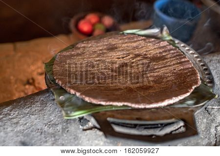 Hot homemade flatbread made of sorghum flour as a part of traditional rustic ethnic Srilankan cuisine