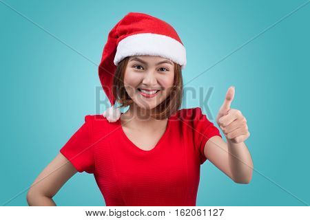 Smiling asian woman portrait with christmas santa hat isolated on blue background.