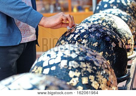 Gilding Gold Leaf To Round Stones Embedded For Worship Buddha.