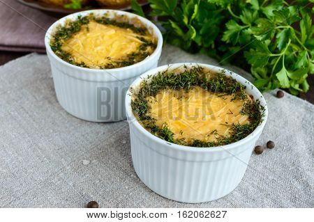 Hot dish of mushrooms chicken baked in a creamy sauce (bechamel) under a cheese crust green decoration in small ceramic bowls on a dark background. Russian