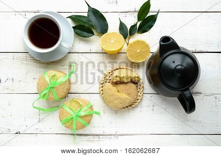 Shortbread lemon flavored cookies: a broken and connected green ribbon for a gift. Teapot and fresh lemon on a white wooden background. The top view.