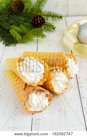 Crispy honey wafers in the form of cones filled with air vanilla cream (ice cream) on a white background. Close-up. Treats for the party.