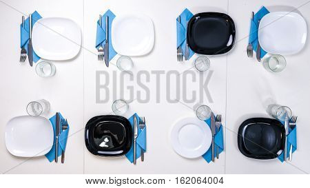 table setting for eight persons with white and black plates, glasses and napkins, top view