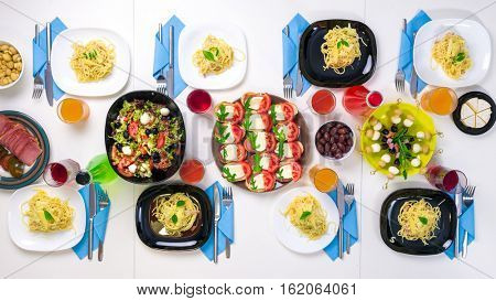 beautiful table setting with colorful dishes, drinks and pasta portions for eight, top view