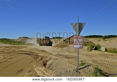 A front end loader tractor with a bucket transports a load of sand in a mining area