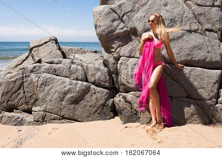 Young slender woman on the sea rocky shore in a pink swimming suit and a pink fabric stand near the rock.