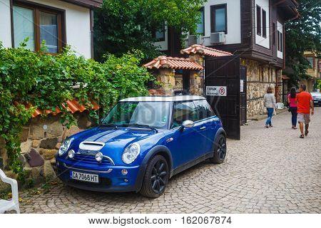 Nesebar Bulgaria - September 06 2014: Blue car Mini Cooper in a narrow street of the old town of Nessebar Bulgaria.