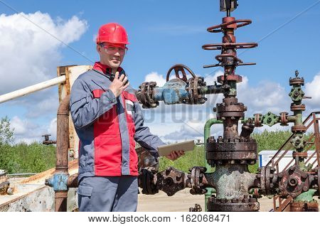 Worker near wellhead valve holding tablet computer and radio and wearing red helmet in the oilfield. Oil and gas concept.