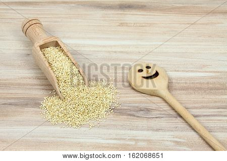 Organic white quinoa seed lat. Chenopodium quinoa in wooden spoon. White quinoa seeds on wooden background.