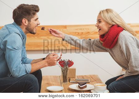 Eat this. Happy loving couple is dating in cafeteria. Woman is feeding her boyfriend with sweet cake. Man is holding cup of coffee and laughing