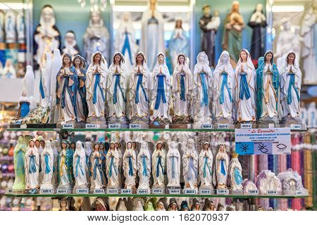 Lourdes France - June 21 2016: Set of different statues of Our Lady of Lourdes in in one of the many religious paraphernalia shops