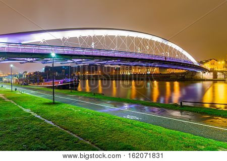 View of Lovers bridge from riverside park at night in Krakow