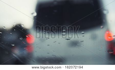Car glass on a rainy day - defocused background. Moving waterdrops in the wipers of the windshield, close up, horizontal