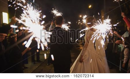 Sparkler in hands on a wedding - bride, groom and guests holding lights in hands, horizontal