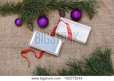 Christmas gift box with a smartphone among Christmas decorations on a burlap background