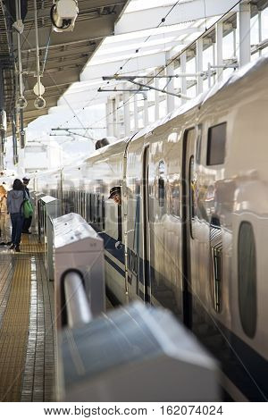 HIROSHIMA, JAPAN - OCTOBER 10, 2016: Unidentified womn at Shinkansen N700 speed train at Hiroshima station in Japan. N700 series trains have a maximum speed of 300 km/h.