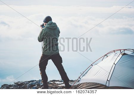 Man photographer with photo camera shooting foggy mountains clouds landscape from tent camping Travel Lifestyle concept adventure vacations outdoor