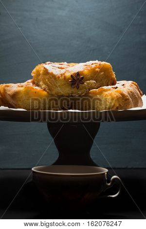 Apple pie in the slit on the plate and tea Cup on black background