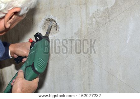 Man holding electric chiseling machine and making a hole in a concrete wall, with space for copy text