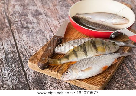 Fresh river fish, perch and roach, on a cutting board and in a frying pan on an old wooden table.
