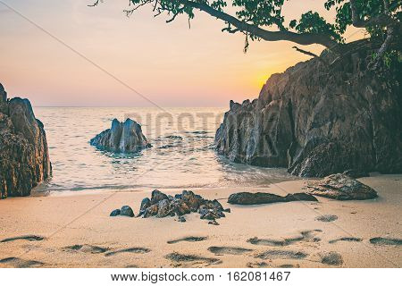 Beautiful seascape. Sea sand with footsteps and rock at the sunset. Nature composition. Thai beach in sunset time in Koh Chang island, Thailand.