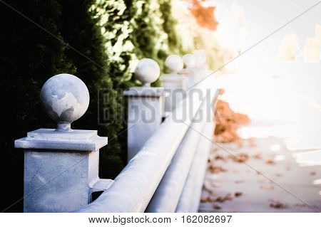 Guardrail stretching into the distance along a sidewalk covered in leaves.
