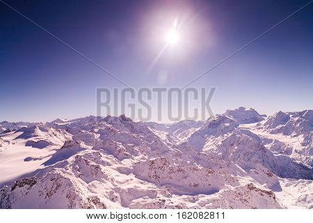 winter sky extremely highly mountains wind clouds sun beam bokeh abstract background