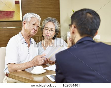 senior asian couple looking skeptical during meeting with insurance agent