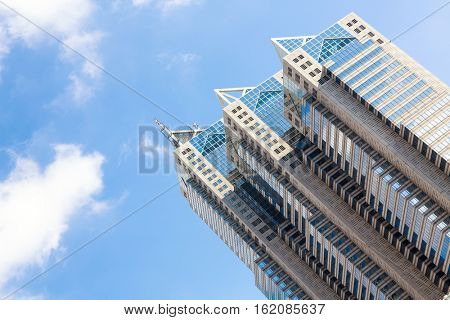 TOKYO, JAPAN - JUNE 23, 2016 -  The Shinjuku Park Tower against blue sky  and white cloud background.The second tallest skyscraper in Shinjuku, designed by Kenzo Tange. Tokyo, Japan.