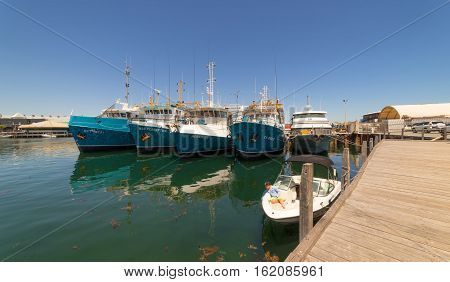 PERTH AUSTRALIA - November 5 2016 : Fishing boats/ships in harbour in Fremantle with the reflection on water .