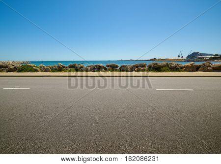 asphalt road on sunny summer day near the water
