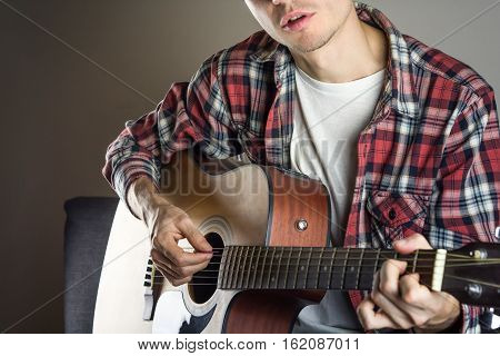 Male musician singing song. Young male person in casual shirt plays acoustic guitar with a pick and sings