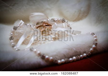 Wedding golden rings garter & necklace on the fur