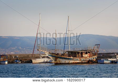 Nesebar Bulgaria - September 10 2014: Old rusty ship at the dock in the port of the old town of Nessebar on the Black Sea coast.