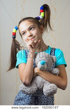 11 year old girl with funny tails hugging a teddy bear
