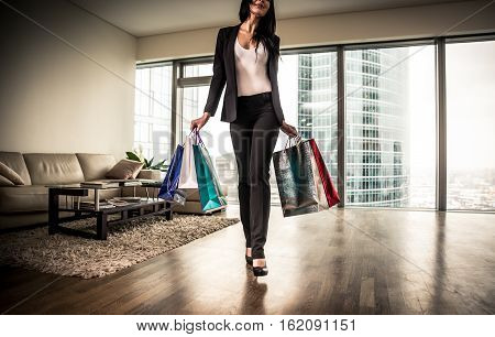 Rich woman going out for shopping with bags