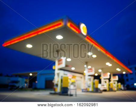 abstract blurred of gas station or petrol station with dark blue sky during twilight time in Malaysia.