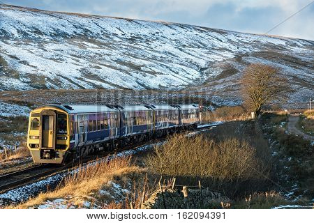 Settle, UK - 10 November 2016. An early evening Northern service commuter train passes through Little Dale in the Yorkshire Dales as it approaches Ribblehead viaduct station on the way to Leeds.  Autumn snow covers the hills of the Yorkshire Dales Nationa