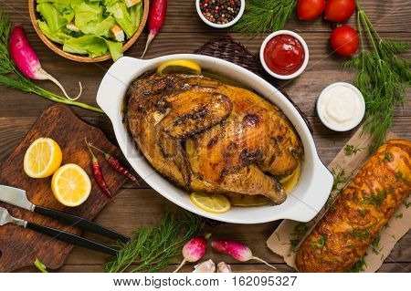 Grilled chicken marinated in balsamic sauce, spicy Italian herbs and fresh lemon. Restaurant supply on a wooden table. Close-up