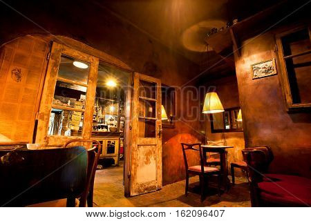 KRAKOW, POLAND - JUL 31, 2014: Wooden furniture doors and lamps inside the cafe in the style of old apartment on July 31, 2014. Krakow with popul. of 800000 people has 2.35 mill. foreign tourists annually.