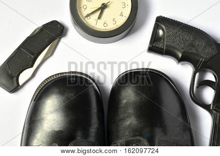 A knife hikes, black hiking boots, alarm clock and back gun on white background isolate