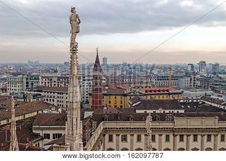 MILAN ITALY - DECEMBER 11 2016: View over Milan from the top of the gothic cathedral Duomo di Milano (Milan Cathedral) Italy. Church's roof statues in the foreground skyscrapers of the city in the background.