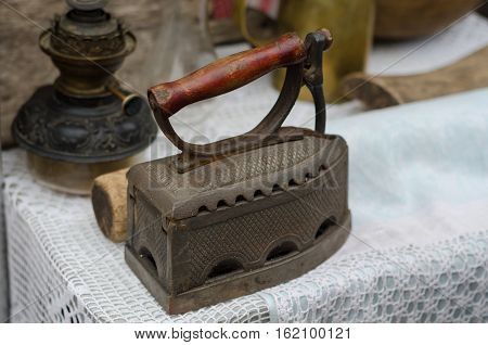 old fashioned retro metallized heavy antique iron tool for ironing with decorative steel and wooden handle with animal head on wood table