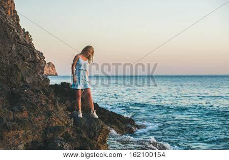 Young blond tourist woman in blue dress standing on natural rocks by the sea at sunset and looking down at still water. Kleopatra beach, Alanya, Mediterranean region, Turkey