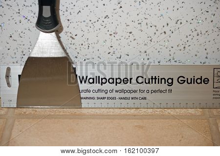 A wallpaper scraper and wallpaper cutting guide tool.