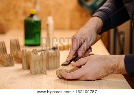 Carpenter hands cutting wood with chisel closeup