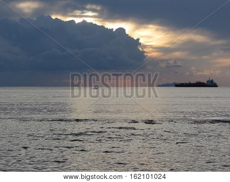 Warm sea sunset with cargo ship and a small fishing boat at the horizon . Giants cumulonimbus clouds are in the sky. Tuscany Italy