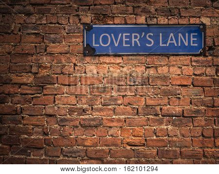 Lover's Lane Sign On A Grungy Old Red Brick Wall