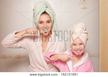 Mother and little daughter with toothbrushes.