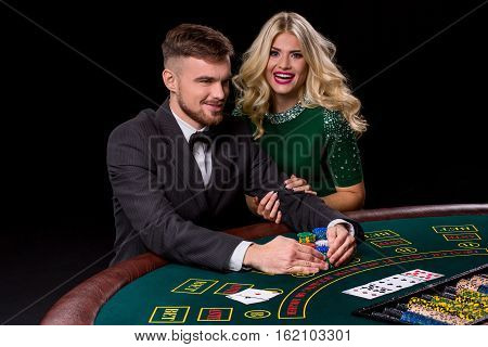 View of young, confident, man with the lady while he's playing poker game. The blonde looks into the camera and smiling